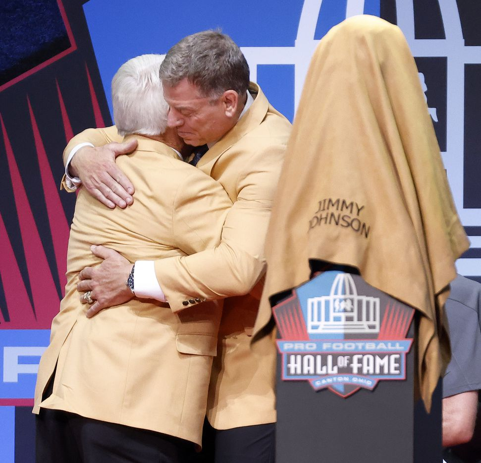 Pro Football Hall of Fame inductee Jimmy Johnson of the Dallas Cowboys (left) receives a hug from his former quarterback and presenter Troy Aikman before the bust reveal during the Centennial Class of 2020 enshrinement ceremony at Tom Benson Hall of Fame Stadium in Canton, Ohio, Saturday, August 7, 2021. (Tom Fox/The Dallas Morning News)