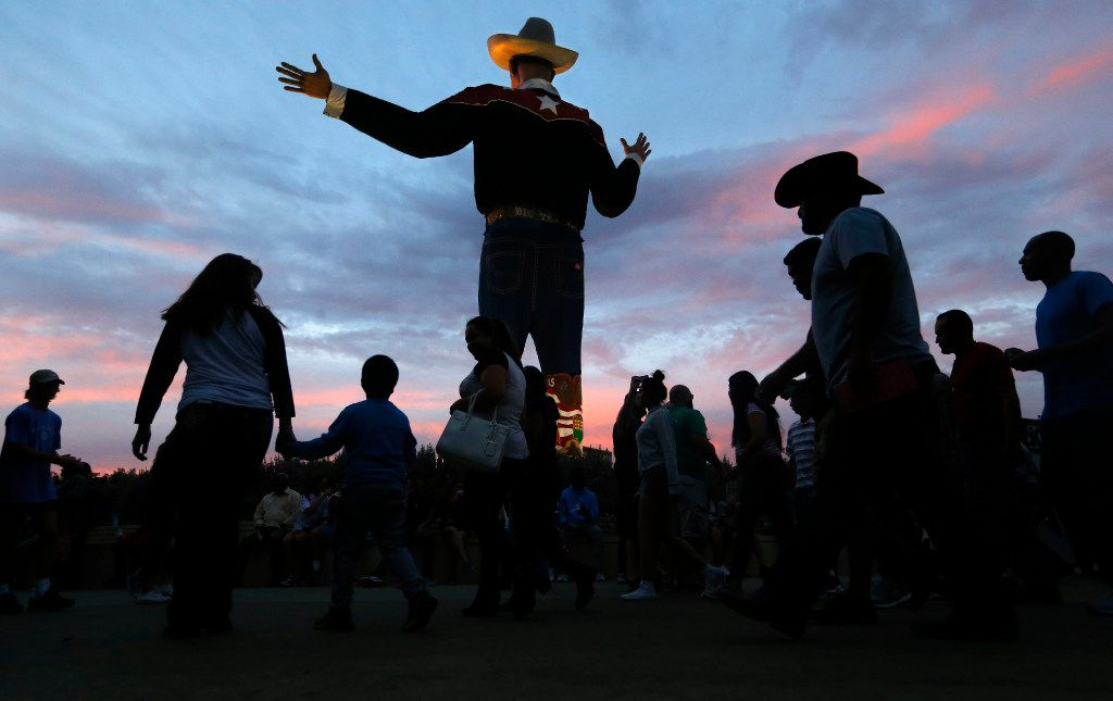 As the sun sets on the last day of the State Fair of Texas, fairgoers pass thru Big Tex Circle at Fair Park in Dallas, Sunday, October 23, 2016. (Tom Fox/The Dallas Morning News)