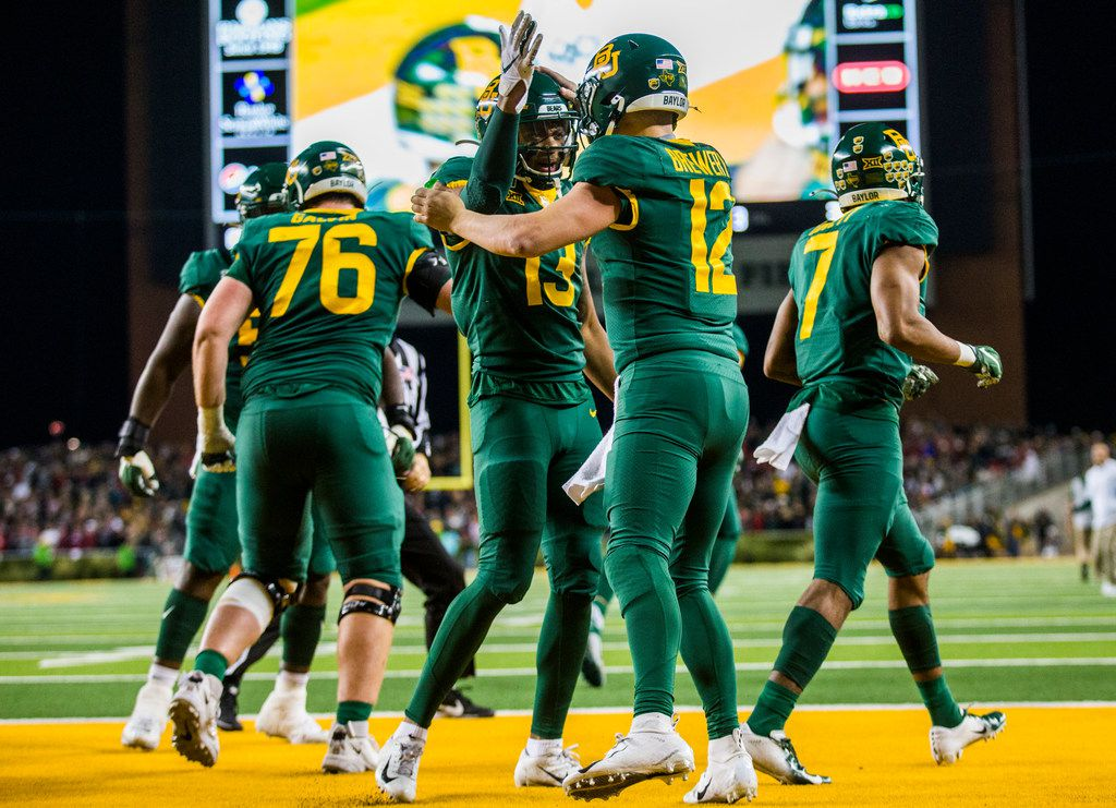 FILE - Baylor quarterback Charlie Brewer (12) celebrates a touchdown with wide receiver R.J. Sneed (13) during the second quarter of a game against Oklahoma on Saturday, Nov. 16, 2019, at McLane Stadium in Waco.