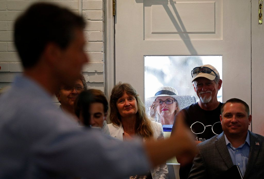 A woman watches U.S. Rep. Beto O'Rourke through a window during a town hall at the Historic Santa Fe Train Depot in Gainesville.