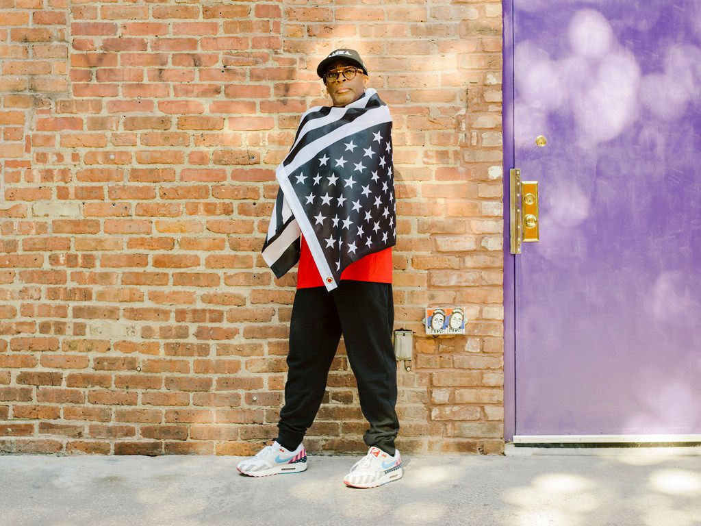 Director Spike Lee drapes himself in an upside-down, black-and-white American flag in New York last month. In BlackKKlansman, Lee uses the true story of a black police officer infiltrating the Ku Klux Klan in Colorado in the 1970s to once again grapple with American racial terrorism.