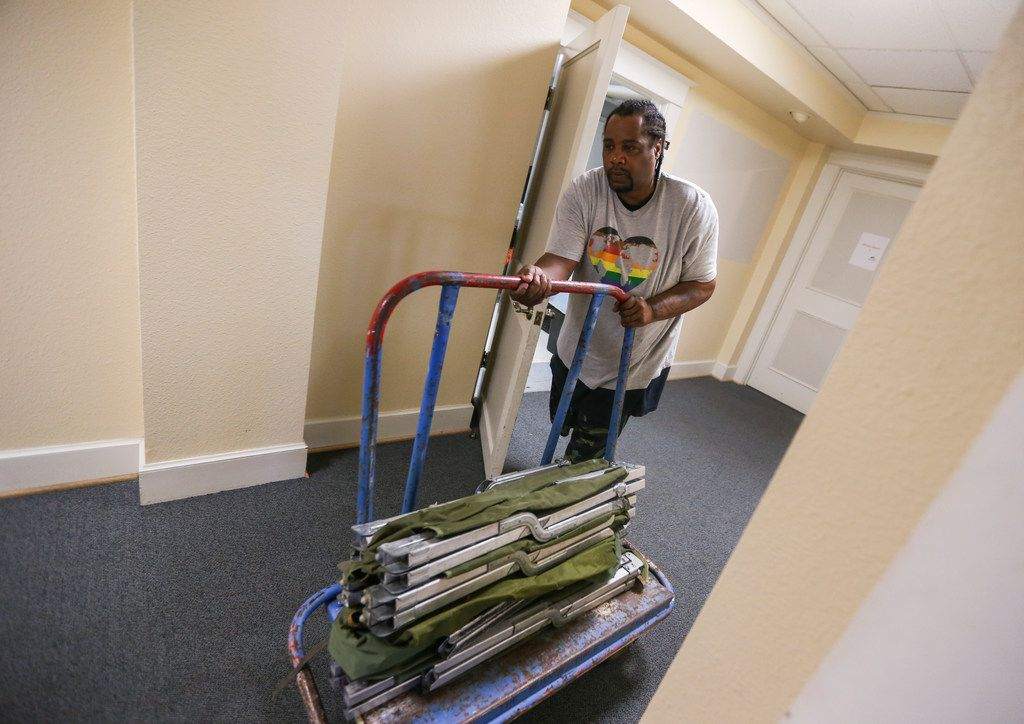 Louis Wright, of Dallas, pushes a dolly full of cots at Oak Lawn United Methodist Church in Dallas on Thursday. The church is in the final stages of preparing to receive migrants asylum-seeking migrants on Saturday.