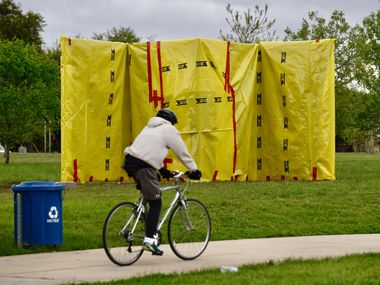 A man rode a bicycle in front of the covered monument honoring musicians Jimmie and Stevie Ray Vaughan at Kiest Park in Dallas in March.