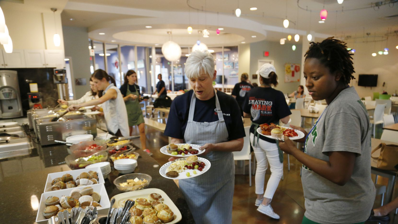 A new fundraising cookbook from Ronald McDonald House of Dallas features recipes from top chefs. Here, employees from Genband help prepare breakfast for the organization.