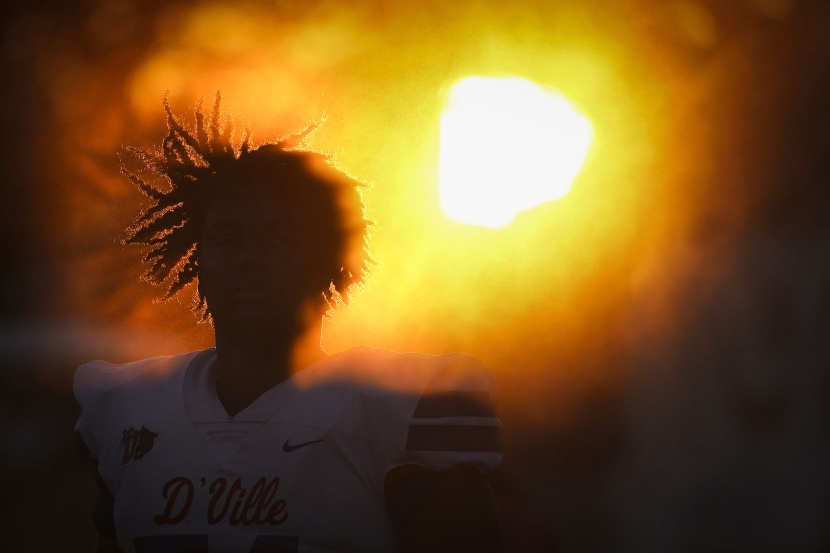 Duncanville offensive lineman Jerry Scales is shrouded in the mist from a cooling station on the sidelines as the sun sets during the first half of a high school football game against Mater Dei on Friday, Aug. 27, 2021, in Duncanville. (Smiley N. Pool/The Dallas Morning News)