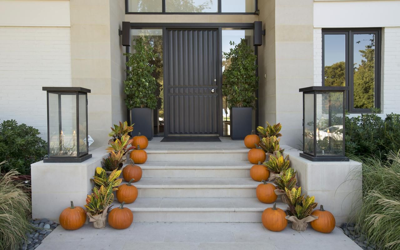 Placing colorful crotons alongside a row of orange pumpkins (above) is a simple, modern way to decorate the path up the steps to a front door. Symmetry is a priority in creating the look, says Wood.