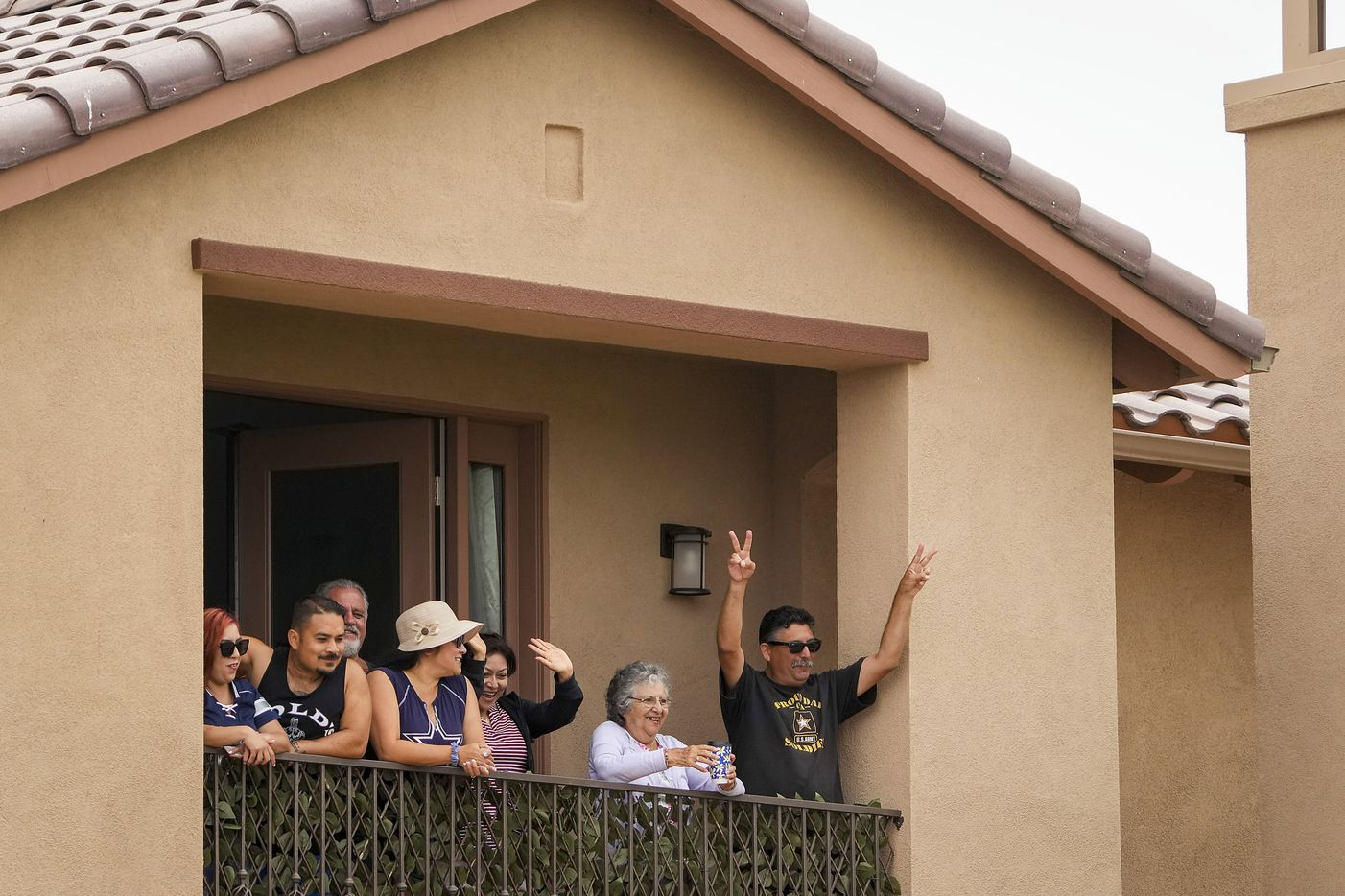 People cheer as they watch the Dallas Cowboys practice at training camp from the balcony of a house adjacent to the team's complex on Sunday, July 25, 2021, in Oxnard, Calif.