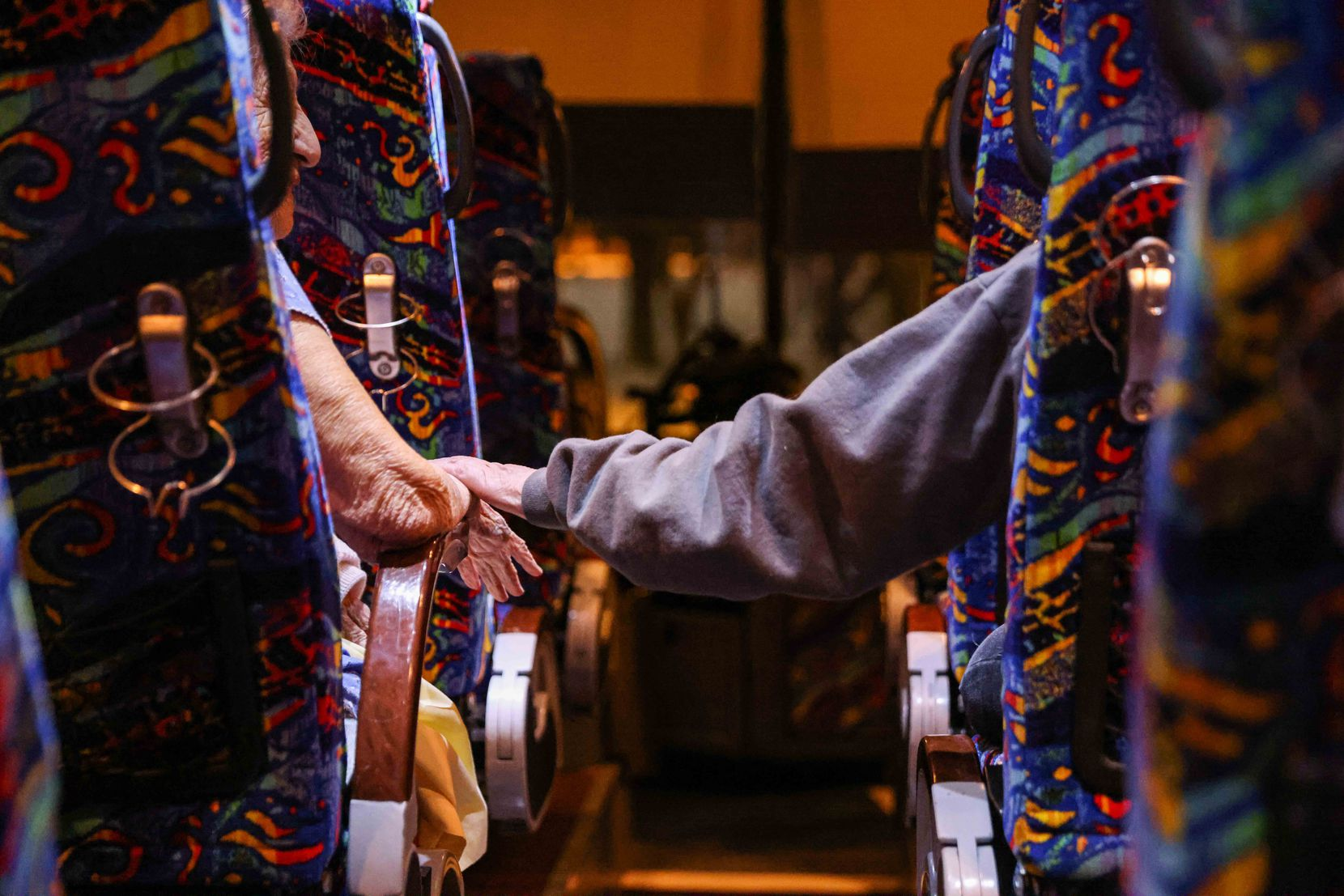Gloria Sanders, 76, reaches for her mother's arm, Maria Barajas, 100, as it rests on the armrest of her seat to try to calm her down as they prepare to spend the night on a charter bus that served as a warming center at the Pleasant Oaks Recreation Center on Wednesday, February 18, 2021.