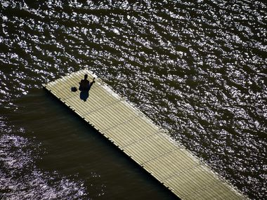 A man sits alone on a boat dock at White Rock Lake in Dallas on Tuesday, March 24, 2020.