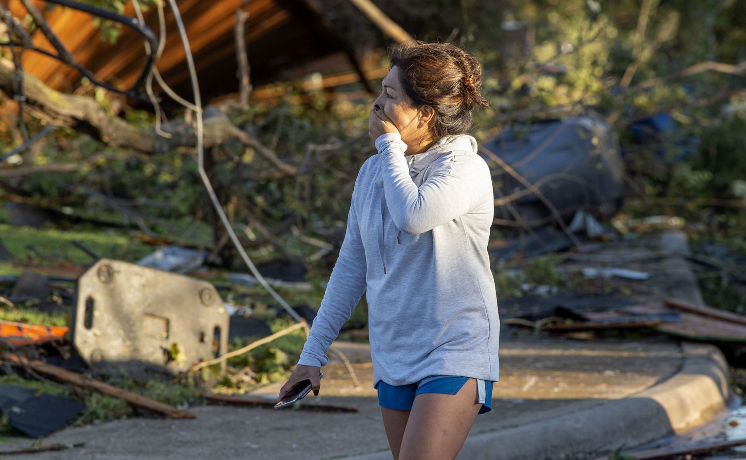 Maricela Chanaa reacts to seeing damage to her neighbors' houses caused by Sunday night's tornado on Monday, Oct. 21, 2019 on Coppedge Lane in Dallas.