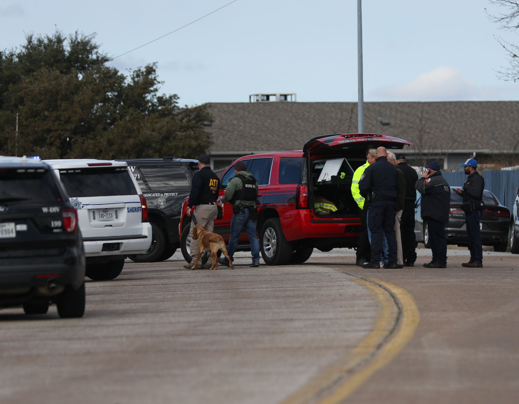 An agent with the Bureau of Alcohol, Tobacco, Firearms and Explosives is seen with a dog at the scene of a shooting at the West Freeway Church of Christ on Sunday.