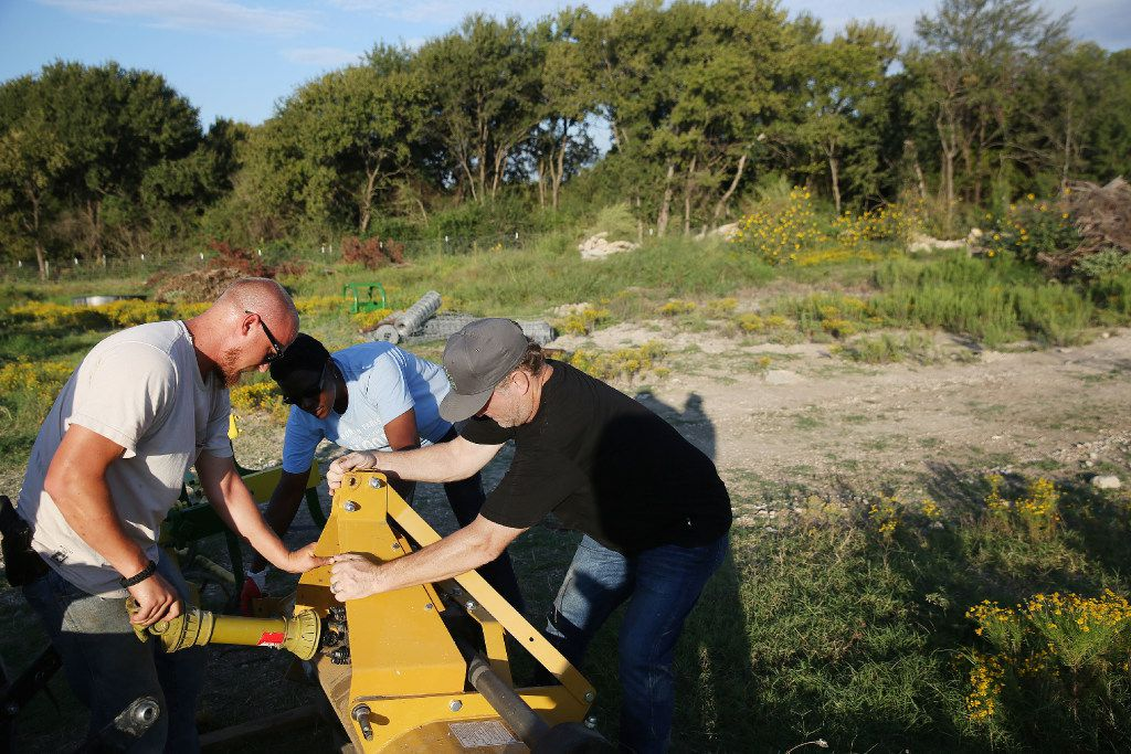 John Treffinger (from left), farm manager Kim High and Daron Babcock attempt to attach a piece of equipment to a tractor at Bonton Farms off Ravenview Road in Dallas. The farm is preparing for their first fall crop on the land. (Andy Jacobsohn/The Dallas Morning News)