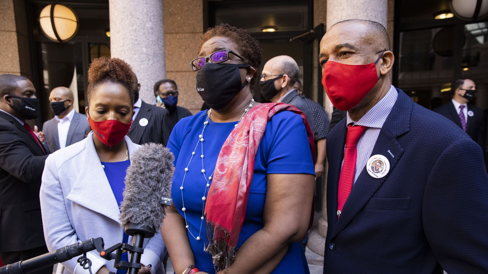 """Allison Jean (center) stands with daughter Alissa Findley (left) and husband Bertrum Jean while speaking to reporters following a press conference where Rep. Carl Sherman, D-DeSoto, introduced House Bill 929, also known as The Botham Jean Act """"Bo's Law"""" Safe at Home, at the Texas Capitol in Austin on Monday, March 29, 2021. Botham Jean was murdered in his Cedars apartment by a Dallas police officer in September 2018. (Juan Figueroa/ The Dallas Morning News)"""