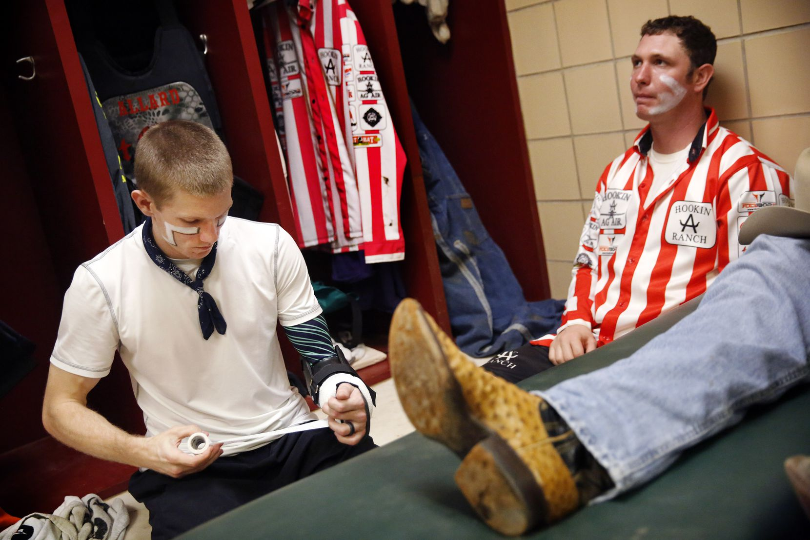 In the Justin Sportsmedicine room, bullfighter Nathan Harp of Tuttle, Oklahoma (left) wraps a brace around his arm as he prepares to go face-to-face with bulls during the PRCA rodeo riding event at the Will Rogers Memorial Coliseum, Saturday, February 2, 2019. Three-time world champion bullfighter Evan Allard (right) of Vinita, Oklahoma has been doing this full time for the past 14 years.