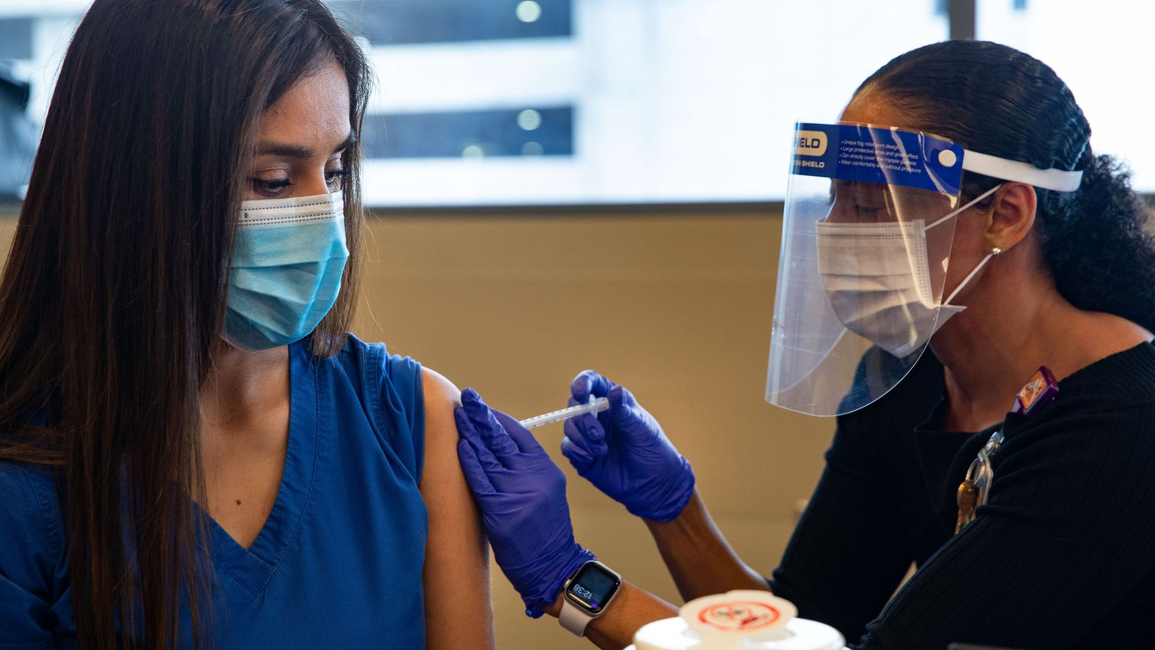 COVID unit nurse Perla Sanchez-Perez (left) receives a dose of the Pfizer COVID-19 vaccination from director of occupational health Stephanie Collins during a media event at Parkland Hospital in Dallas.
