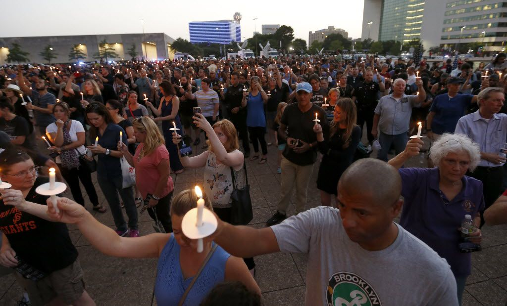 People hold up candles during a candlelight vigil hosted by the Dallas Police Association in honor of the five police officers killed by the ambush attack in the line of duty at Dallas City Hall in downtown Dallas, Monday, July 11, 2016. (Jae S. Lee/The Dallas Morning News)