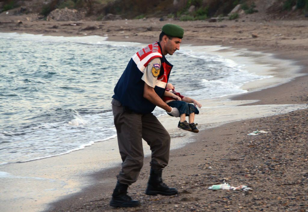 ADDS IDENTIFICATION OF CHILD   A paramilitary police officer carries the lifeless body of Aylan Kurdi, 3, after a number of migrants died and a smaller number were reported missing after boats carrying them to the Greek island of Kos capsized, near the Turkish resort of Bodrum early Wednesday, Sept. 2, 2015. The family — Abdullah, his wife Rehan and their two boys, 3-year-old Aylan and 5-year-old Galip — embarked on the perilous boat journey only after their bid to move to Canada was rejected. The tides also washed up the bodies of Rehan and Galip on Turkey's Bodrum peninsula Wednesday, Abdullah survived the tragedy. (AP Photo/DHA) TURKEY OUT 09042015xPUB