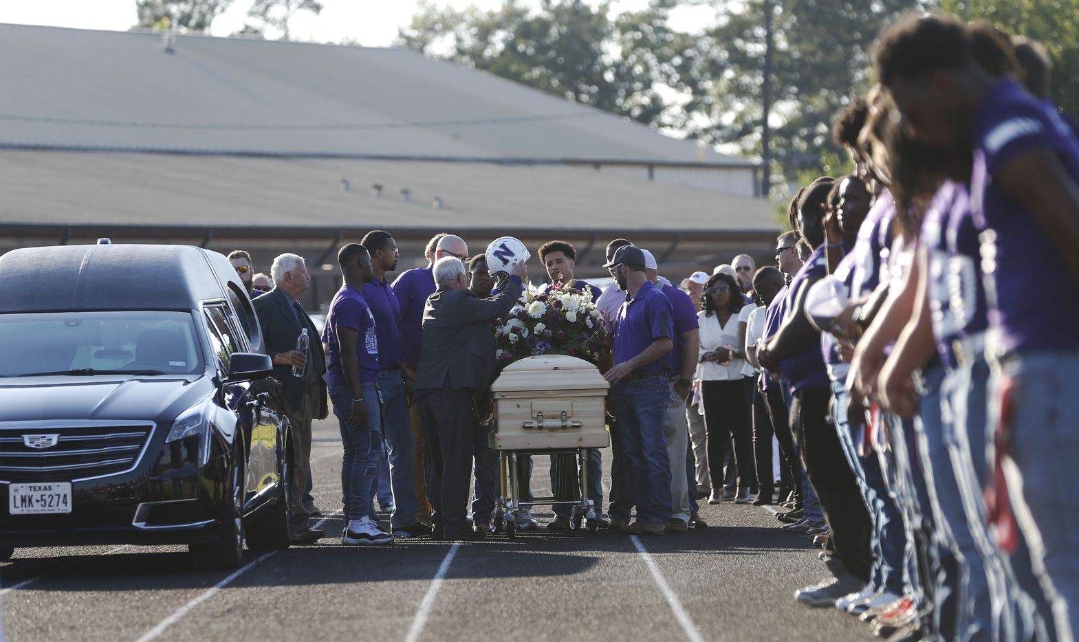"""Pallbearers prepare to take Newton High School head football coach William Theodore """"W.T."""" Johnston onto the field for his memorial service at Curtis Barbay Field at Newton High School in Newton, Texas on Wednesday, May 15, 2019. (Vernon Bryant/The Dallas Morning News)"""