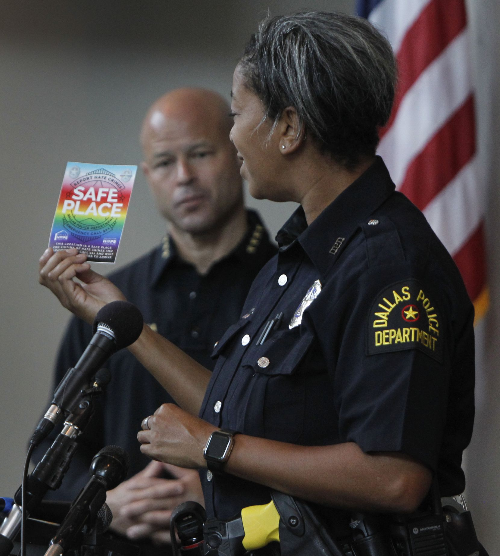 Dallas Police Department's new LGBTQ+ liaison, officer Megan Thomas, displays the Safe Place business designations for potential targets of hate crimes until police can arrive. Police Chief Eddie Garcia looks on in the background. The launch of the Safe Place Program was held at the Dallas police Department headquarters at 1400 Botham Jean Blvd. in Dallas on June 28, 2021. (Steve Hamm/ Special Contributor)