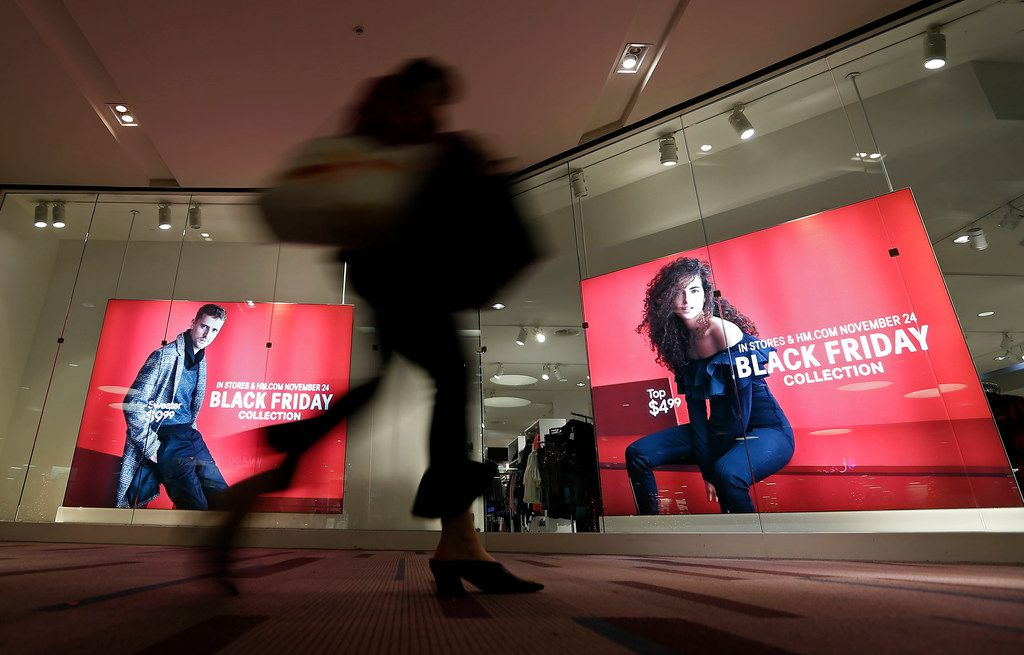 A woman with shopping bags walks by Black Friday sale signs at an H&M store at Galleria Dallas.
