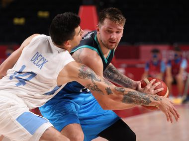 Slovenia's Luka Doncic (77) is defended by Argentina's Gabriel Deck (14) during the postponed 2020 Tokyo Olympics at Saitama Super Arena on Monday, July 26, 2021, in Saitama, Japan.