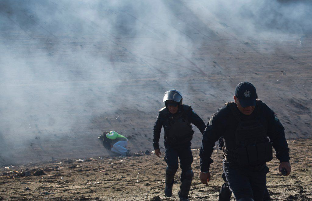 A Honduran migrant lies on the riverbank as Mexican police move away from tear gas fired by U.S. agents at the Mexico-U.S. border in Tijuana, Mexico, Sunday, Nov. 25, 2018, as a group of migrants try to pressure their way into the U.S. The mayor of Tijuana has declared a humanitarian crisis in his border city and says that he has asked the United Nations for aid to deal with the approximately 5,000 Central American migrants who have arrived in the city. (AP Photo/Ramon Espinosa)