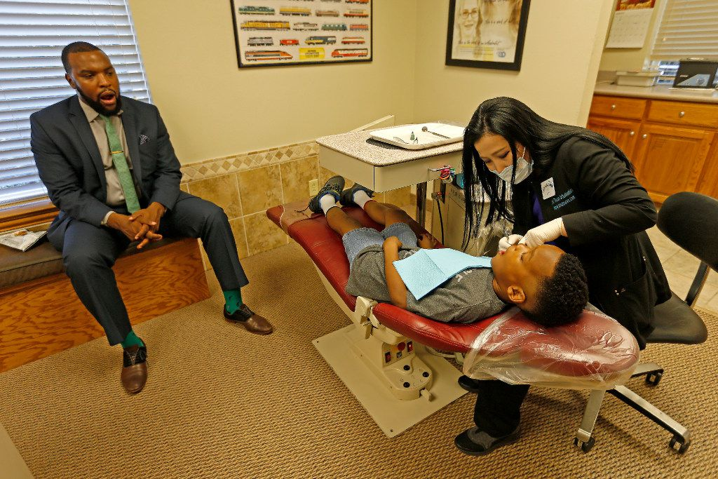 Attorney Lee Merritt (left) watches his 7-year-old son Stacy Merritt, Jr., who has a retainer installed by Registered Dental Assistant Amy Lee at the North Texas Orthodontic Associates' office in Allen.