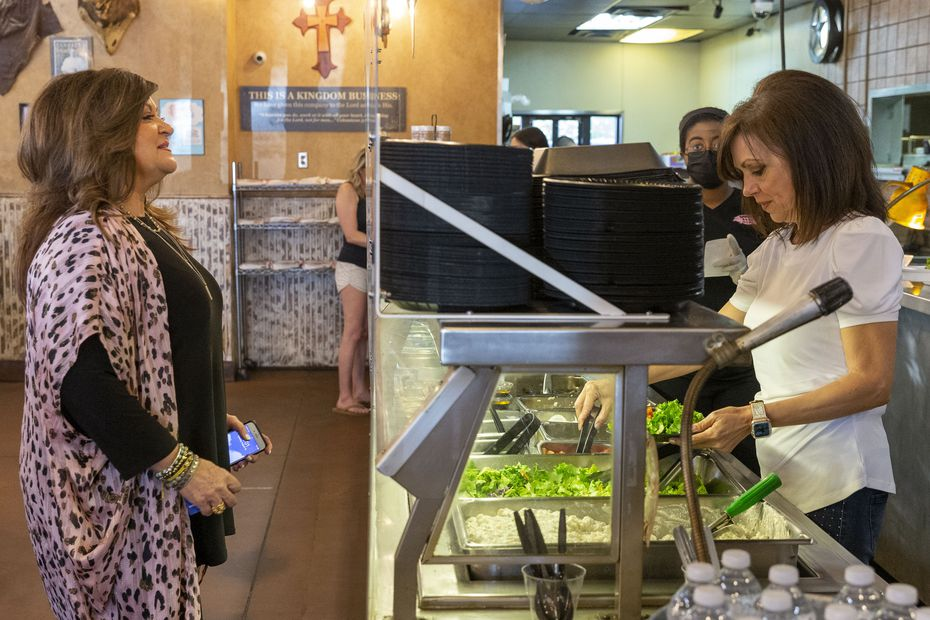 Baker's Ribs co-owner DeeAnna Krier (right) serves a plate of food for customer Debra Camp.