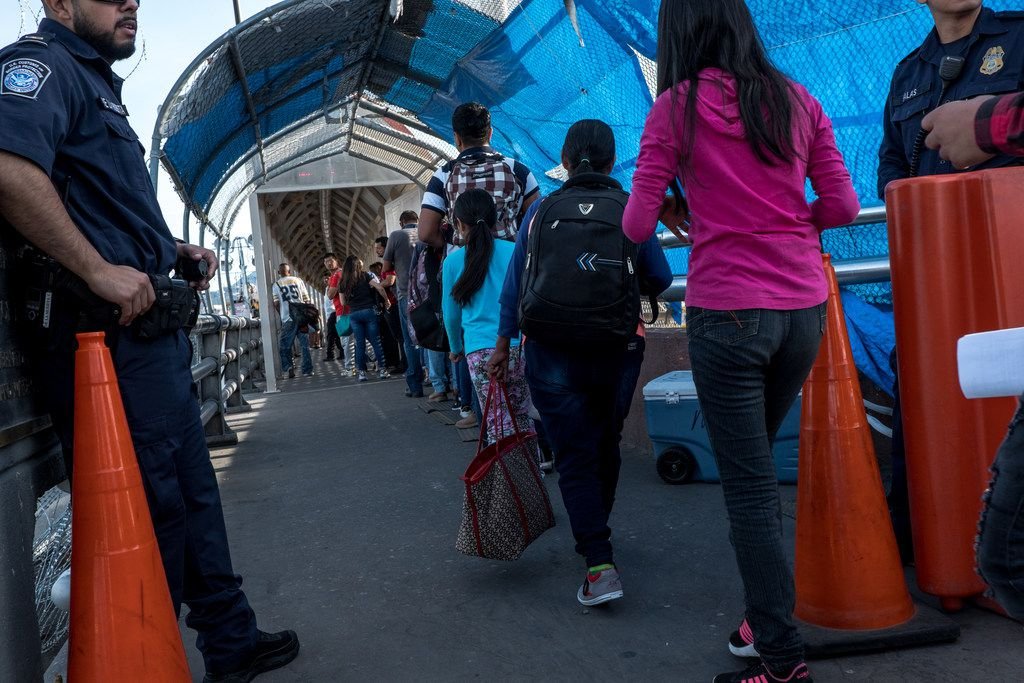 Asylum-seekers from Guatemala walk past a U.S. Customs and Border Protection checkpoint on the Paso del Norte Bridge in Juarez on August 1 as they are escorted for their asylum court cases as part of the Migrant Protection Protocols program.