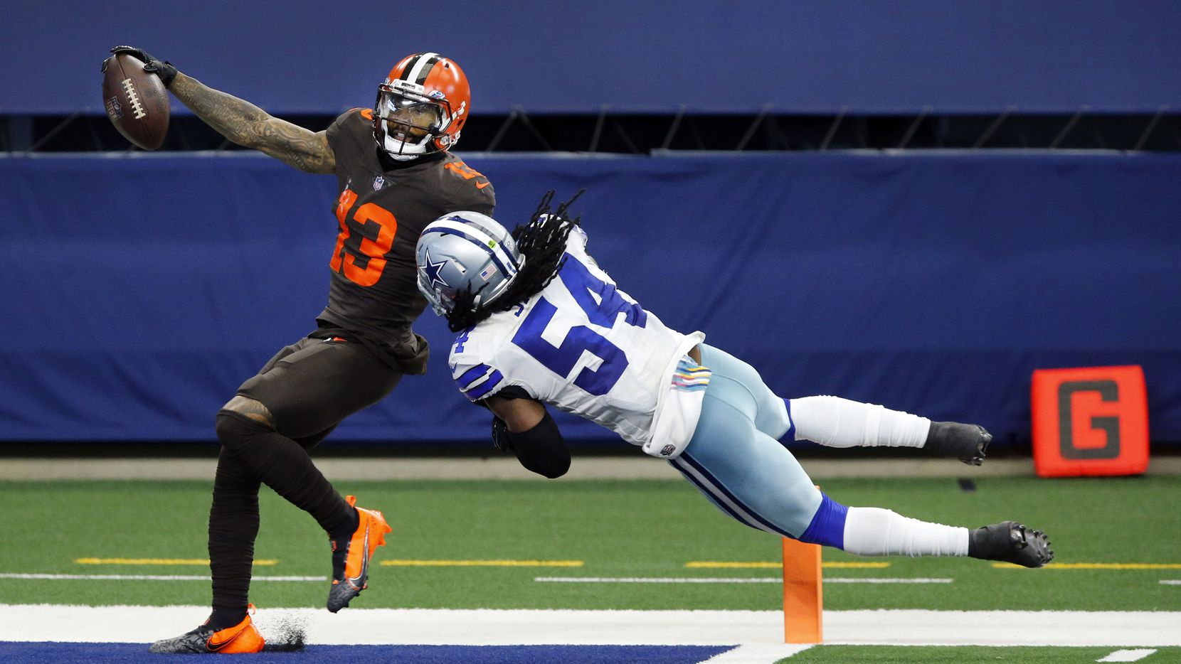 Browns wide receiver Odell Beckham Jr. (13) crosses the goal line for a long forth-quarter touchdown as Cowboys middle linebacker Jaylon Smith (54) hangs on at AT&T Stadium in Arlington on Sunday, Oct. 4, 2020.