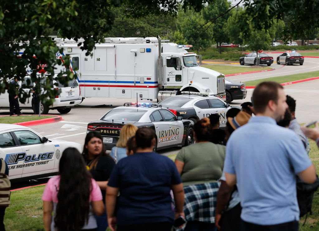 People watch as police investigate after a shooting at North Lake College in Irving.