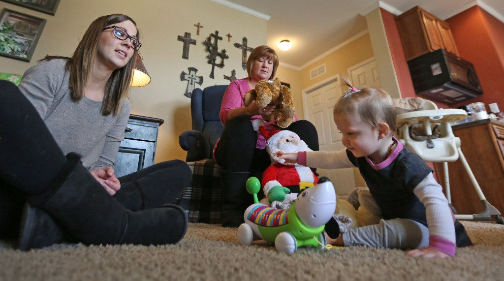 Kelley McKissack, left, plays with 1-year-old daughter Kelcey, right, as grandmother Tracy Thompson enjoys the visit. (Louis DeLuca/The Dallas Morning News)