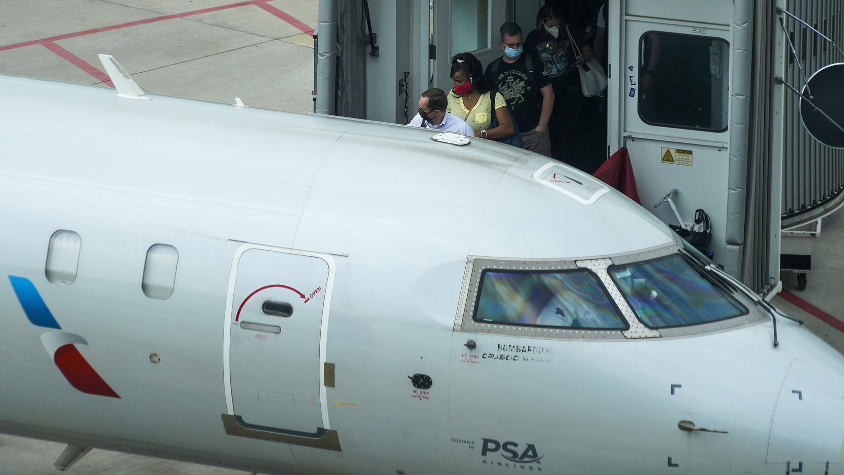 Passengers wearing face coverings board American Eagle flight at Terminal B at DFW International Airport.