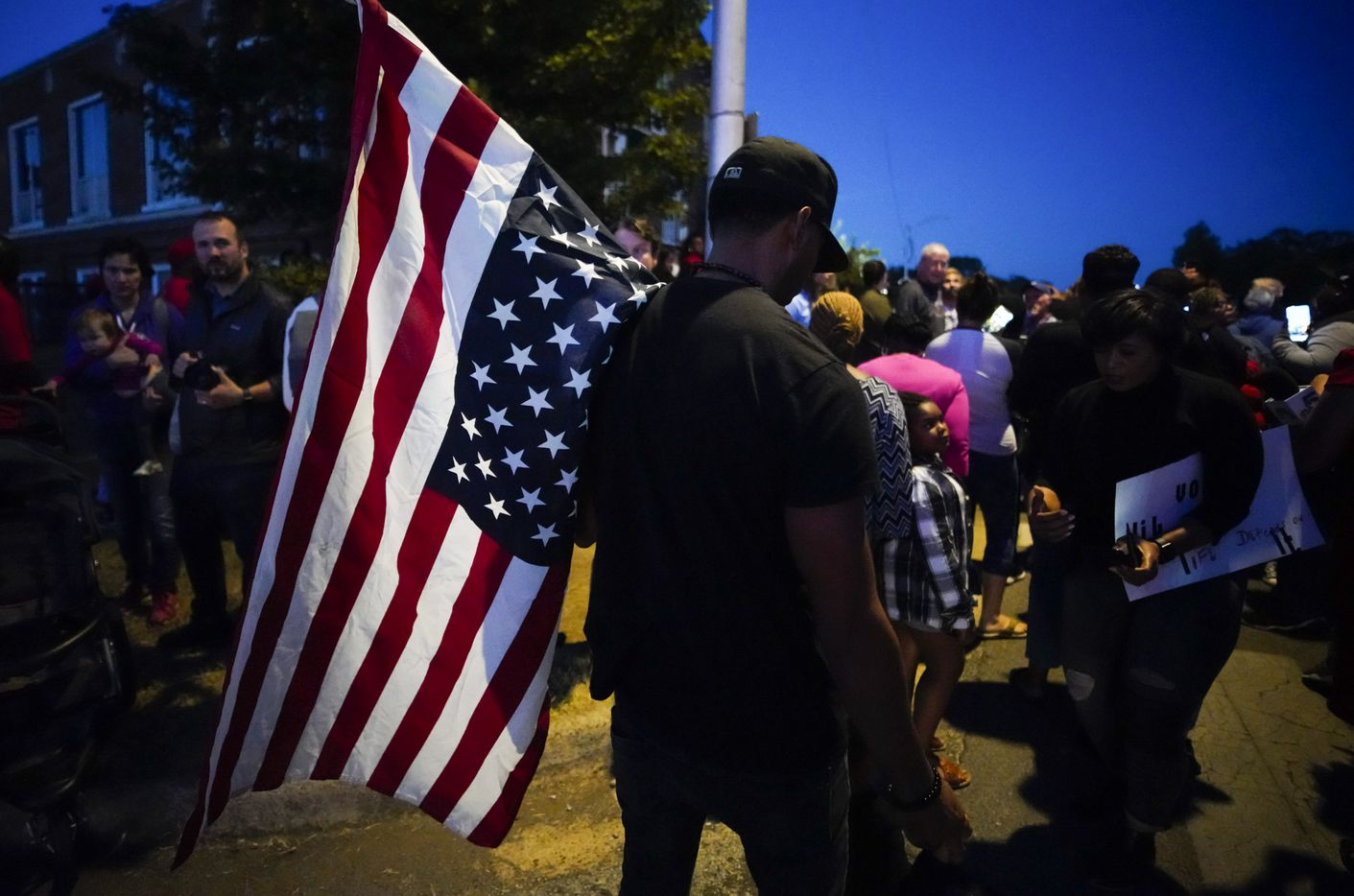 A large crowd of protestors, including a man carrying an upside-down American flag, gathered outside the house where Atatiana Jefferson was shot and killed, during a community vigil for Jefferson on Sunday, Oct. 13, 2019, in Fort Worth.