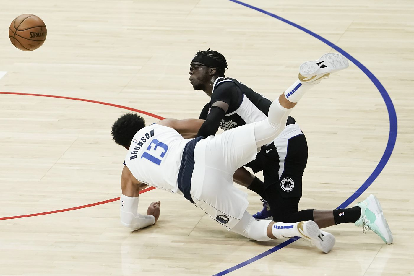 Dallas Mavericks guard Jalen Brunson (13) collides with LA Clippers guard Reggie Jackson (1) chasing a loose ball during the second half of an NBA playoff basketball game at Staples Center on Saturday, May 22, 2021, in Los Angeles.