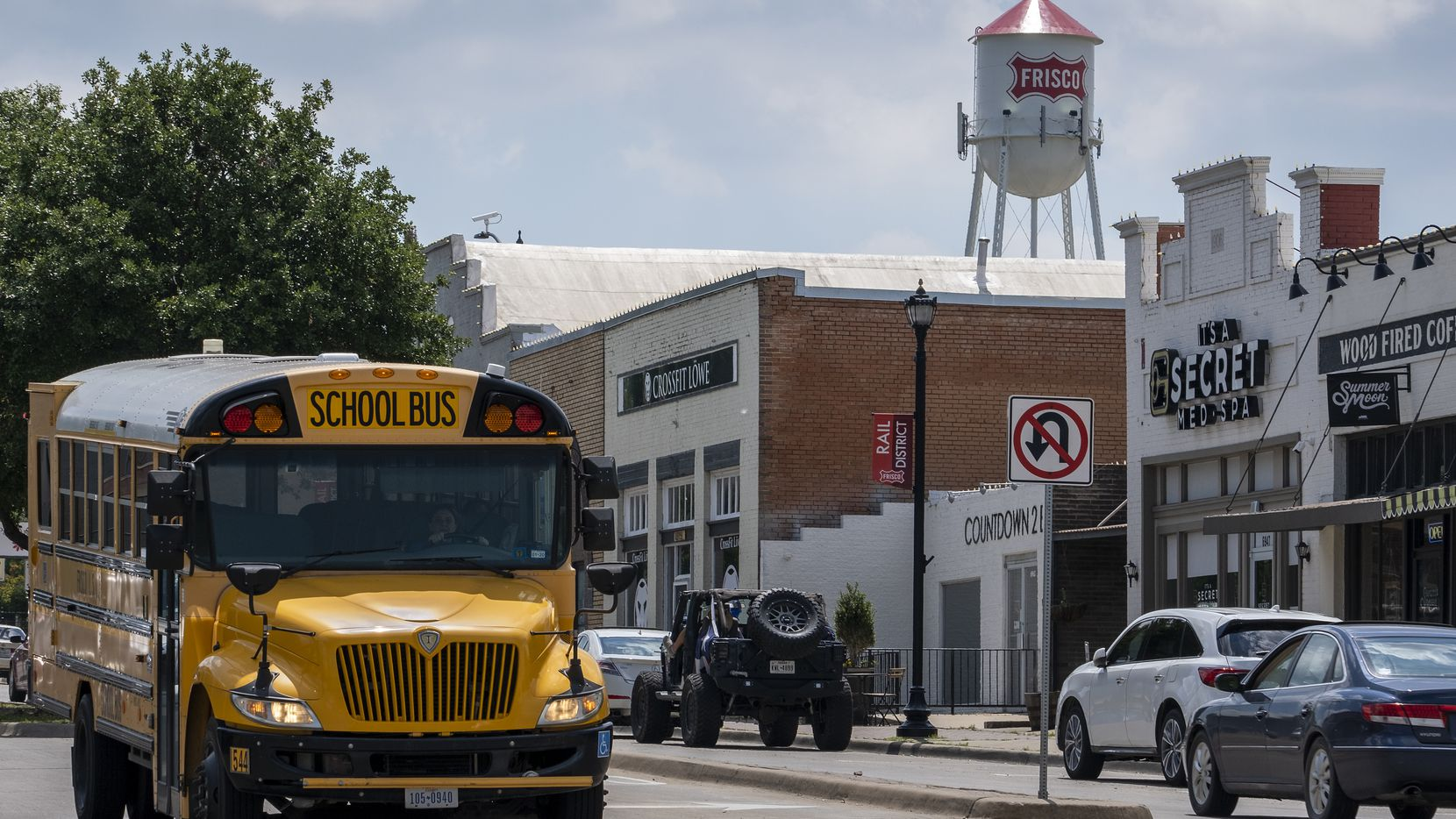 A Frisco ISD school bus passes along Main Street under the city's old iconic water tower. The school district has grown rapidly, along with everything else in this North Texas boomtown.