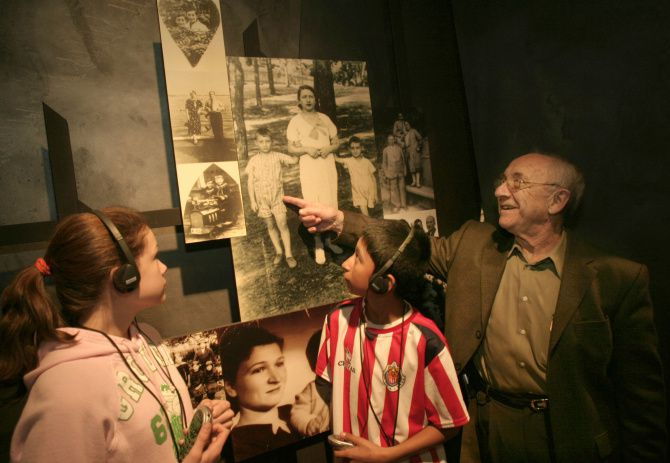 Max Glauben points to himself in a family photo before the war as he stands with Little Elm Lakeside Jr. High seventh-graders Anastasia Seis and Victor Rodriguez at The Dallas Holocaust Museum.
