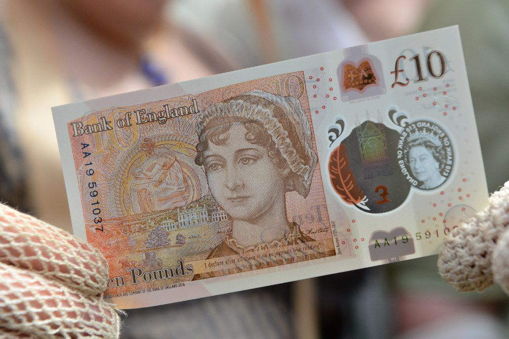 People in period costume pose with one of the Bank of England's new ten pound notes, featuring British author Jane Austen.