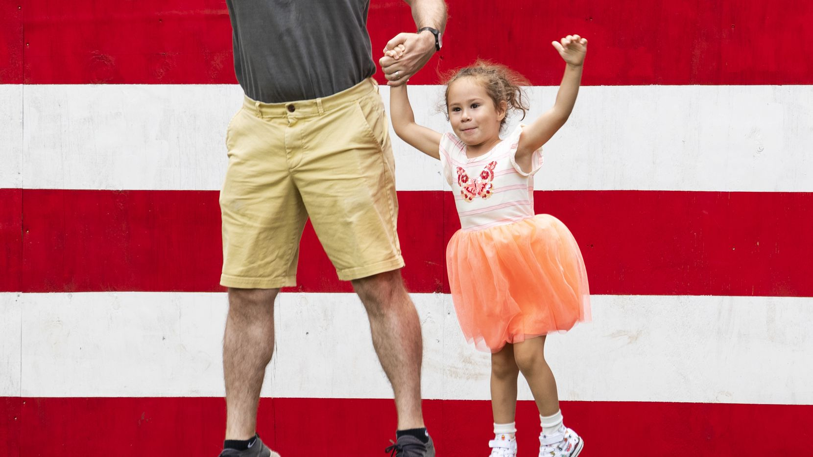 Daphney Mitchell, 4, leaps with her fauther, Jess Mitchell as her mother photographed them by a painted American flag at the Dallas Arboretum on Saturday, July 3, 2021.