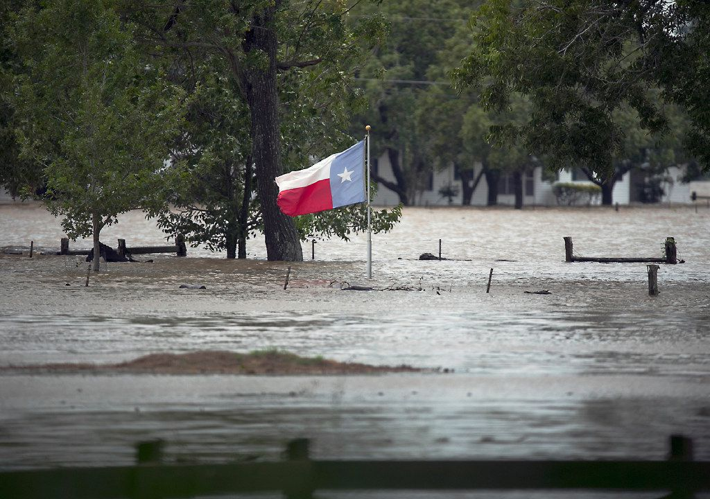 A Texas flag flies over floodwaters caused by Tropical Storm Harvey in La Grange, Texas, Monday, Aug. 28, 2017. (Ralph Barrera/Austin American-Statesman via AP)