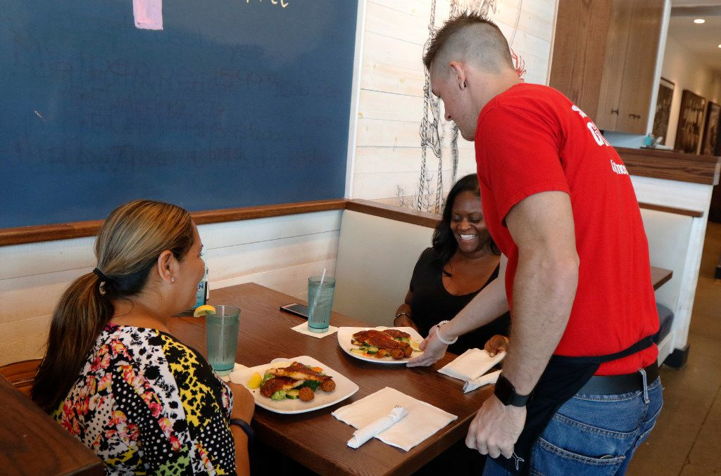 Corey Ahrens, 37, serves lunch to Regina Coter (left) and LaShamda Cole at Fish City Grill in Richardson on Tuesday, July 18, 2017.