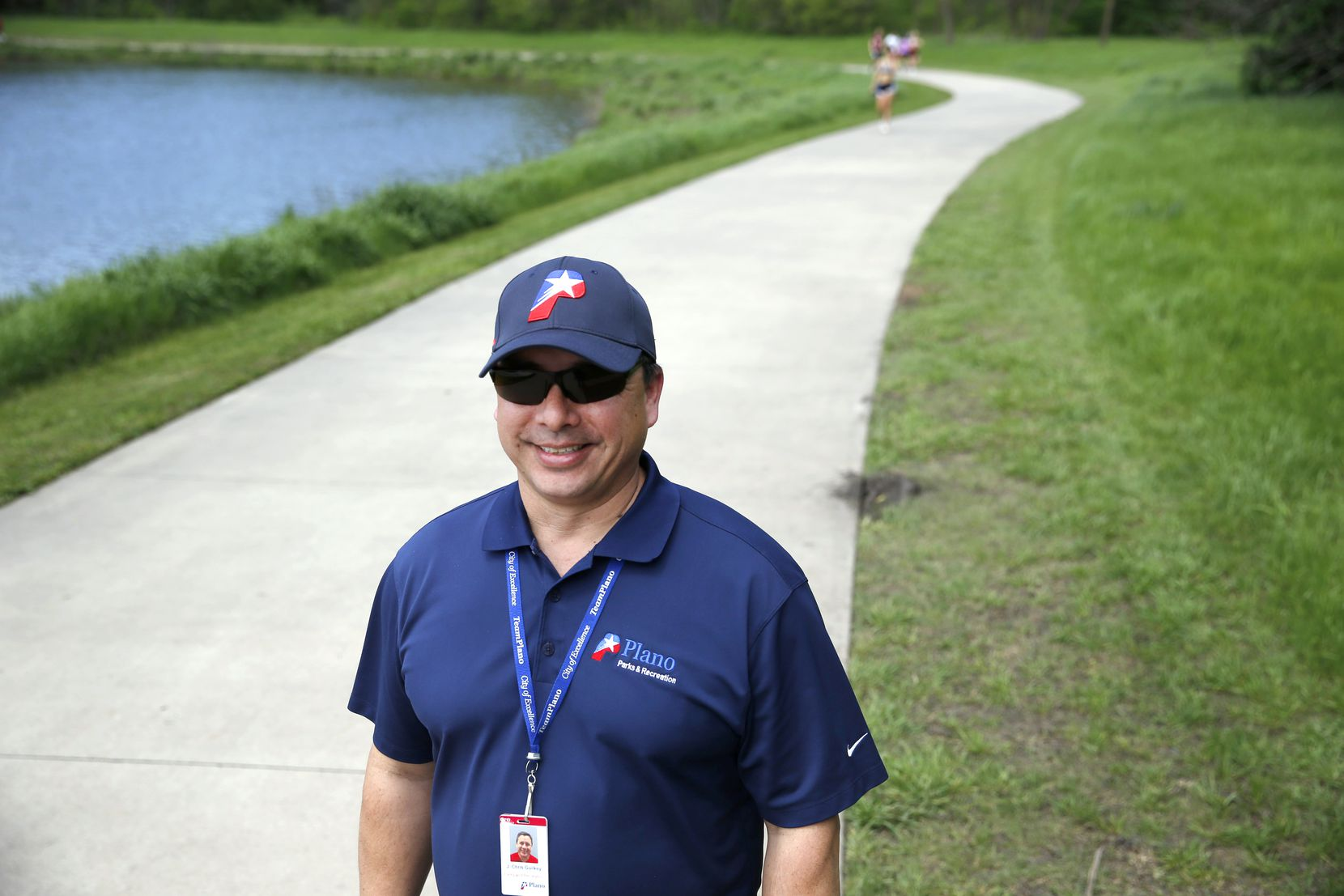 """Chris Guilkey, a business analyst with the Plano Parks and Recreation Department, has also been working as a """"friendly monitor,"""" breaking up groups and encouraging social distancing, at the city's Oak Point Nature Preserve."""