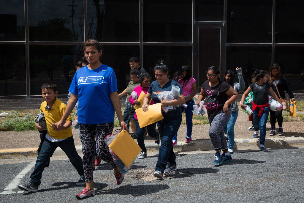 """Immigrants walk to a nearby Catholic Charities relief center after being dropped off at a bus station shortly after release from detention through """"catch and release"""" immigration policy on Sunday in McAllen."""