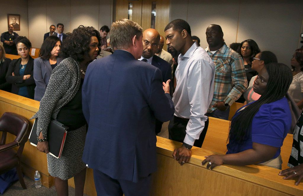 Lead prosecutor Michael Snipes and District Attorney Faith Johnson talk to Odell and Charmaine Edwards after their son's killer was sentenced Wednesday. (Rose Baca/Staff Photographer)