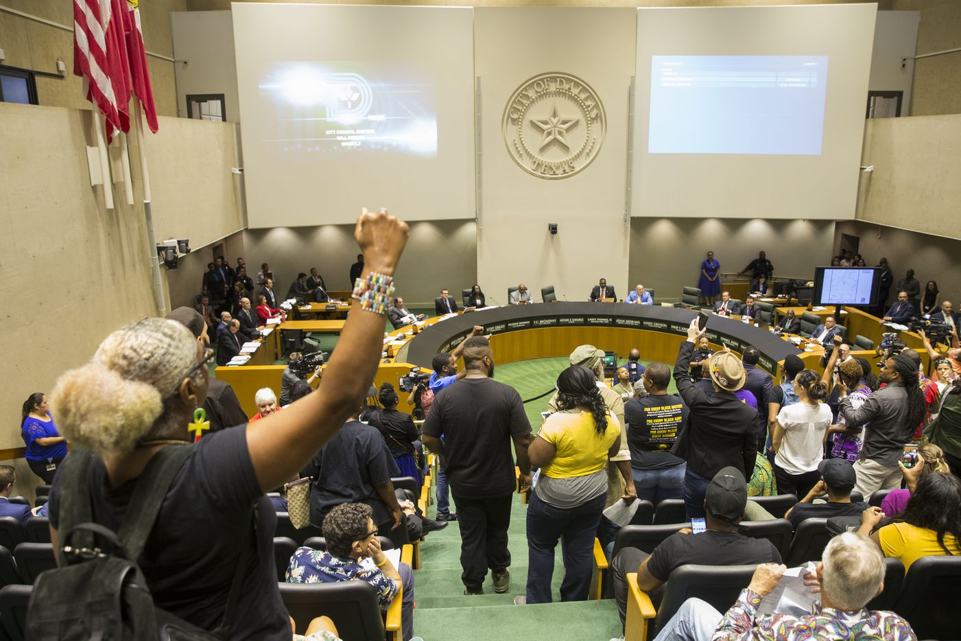 "Protesters raise their fists and yell ""no justice, no peace"" during a city council meeting on Wednesday, September 12, 2018 at Dallas City Hall in Dallas. Next Generation Action Network had a press conference in the Dallas City Hall Flag Room before going into the council chambers where they were told they had to wait until the end of the regular council meeting to voice their concerns. They began chanting ""No Justice, no peace"" then Dallas Mayor Mike Rawlings walked out of the chambers, twice"