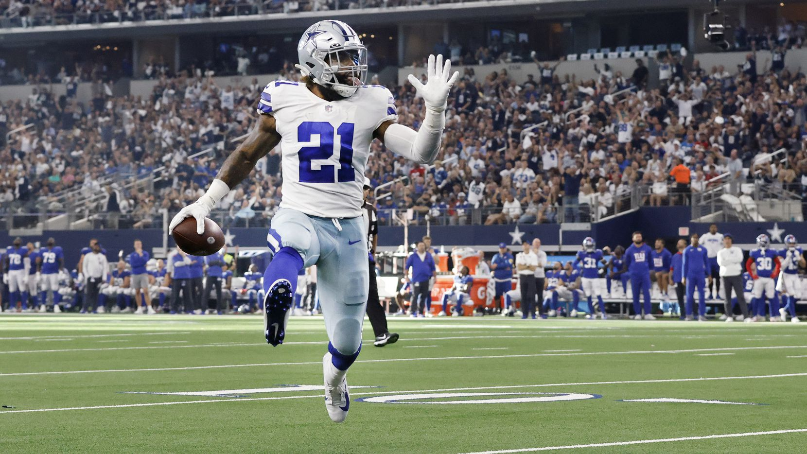 With his tongue hanging out, Dallas Cowboys running back Ezekiel Elliott (21) high steps towards the end zone for a third quarter touchdown against the New York Giants at AT&T Stadium in Arlington, Texas, Sunday, October 10, 2021. (Tom Fox/The Dallas Morning News)