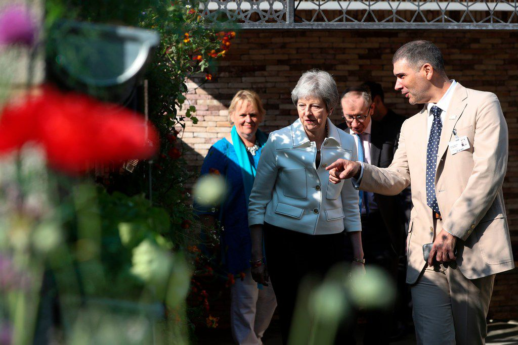 Britain's Prime Minister Theresa May is shown around the Lemon Tree Trust Garden by the trust's Alfonso Montiel (right) of Dallas during a visit the 2018 Chelsea Flower Show in London on May 21.
