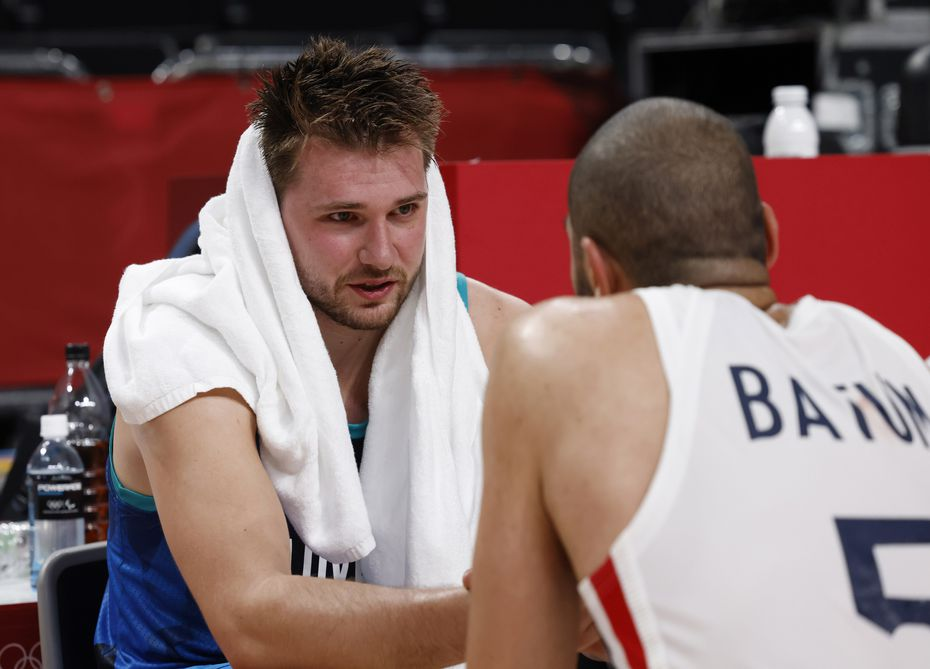 Slovenia's Luka Doncic (77)  talks with France's Nicolas Batum (5) as he sits dejected after losing to France 90-89 in a men's basketball semifinal on Thursday, August 5, 2021, in Saitama, Japan.