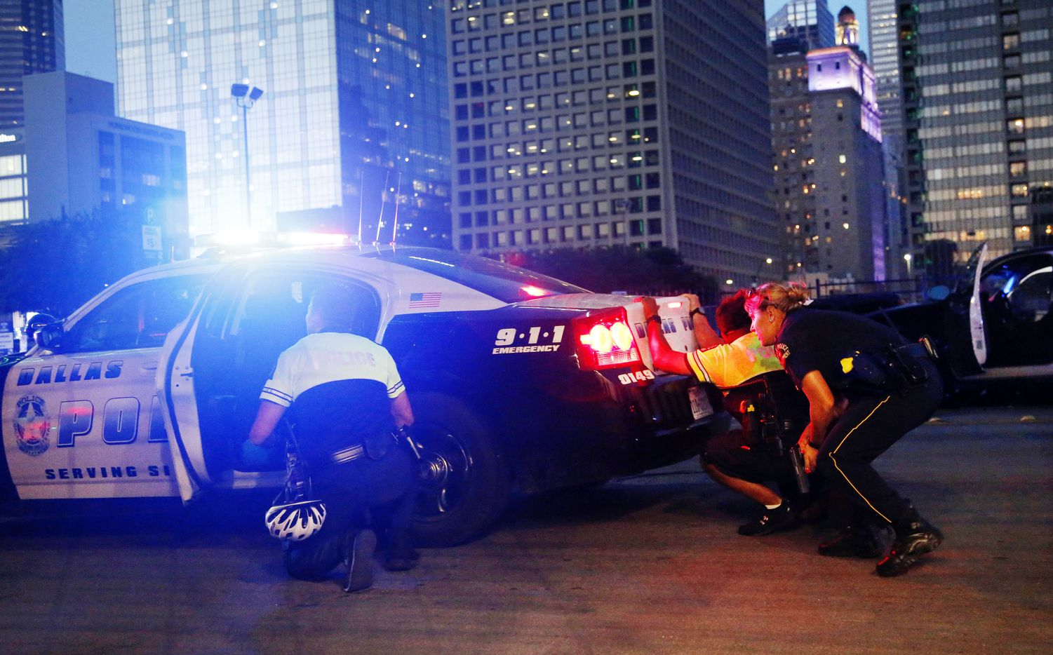 Dallas police officers take cover behind a police cruiser after the gunfire began.
