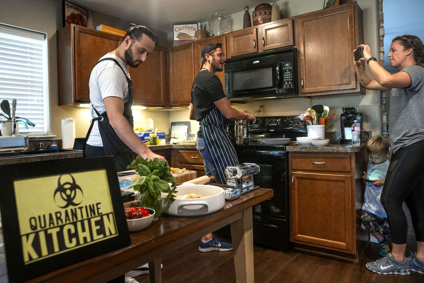 Benchmark Hospitality conference planner Christie Wilson (right) filmed chef Kyle Wilson (center) and sous-chef Kreshnik Mucllari as they prepared pasta shapes to broadcast to other company employees on Facebook Live from Wilson's home in Fort Worth in September.